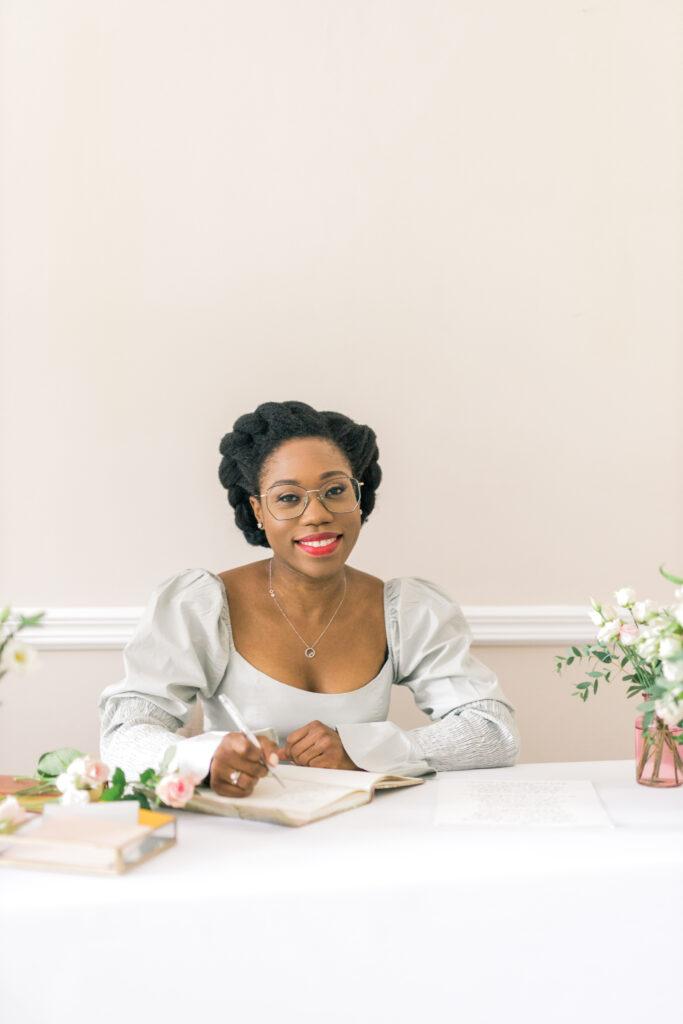 Black woman at a table writing
